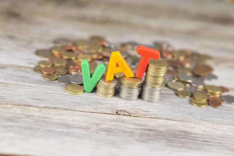 Mehrwertsteuer-Zunahmekonzept mit bunten Plastikbuchstaben auf Stapel von Münzen stockbilder