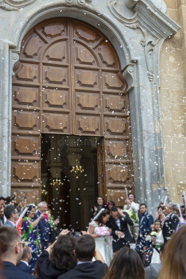 Mei 25, 2019, Marsala, Italië, Italiaans katholiek huwelijk in kerk met vele gasten en begroeting van documenten en rijst stock afbeelding