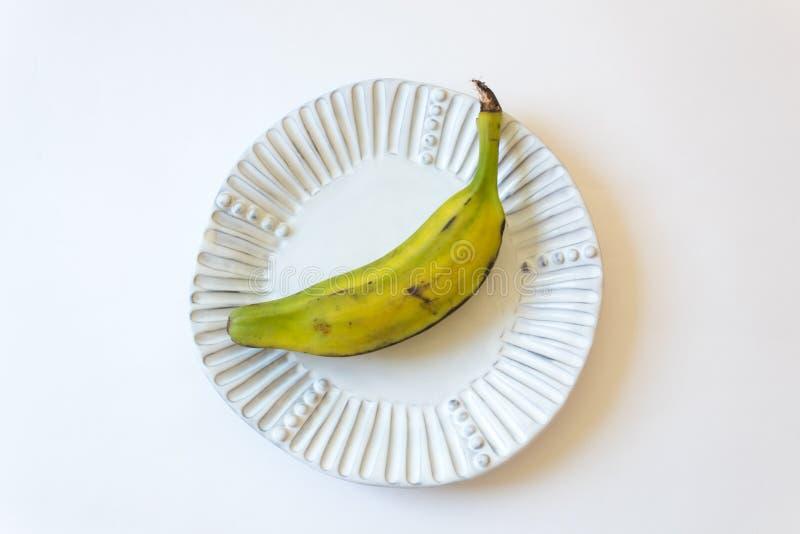 Meia banana madura do Burro, também banana de Orinoco, de Bluggoe, de cavalo, de porco ou de Largo na placa acanelado branca imagem de stock royalty free