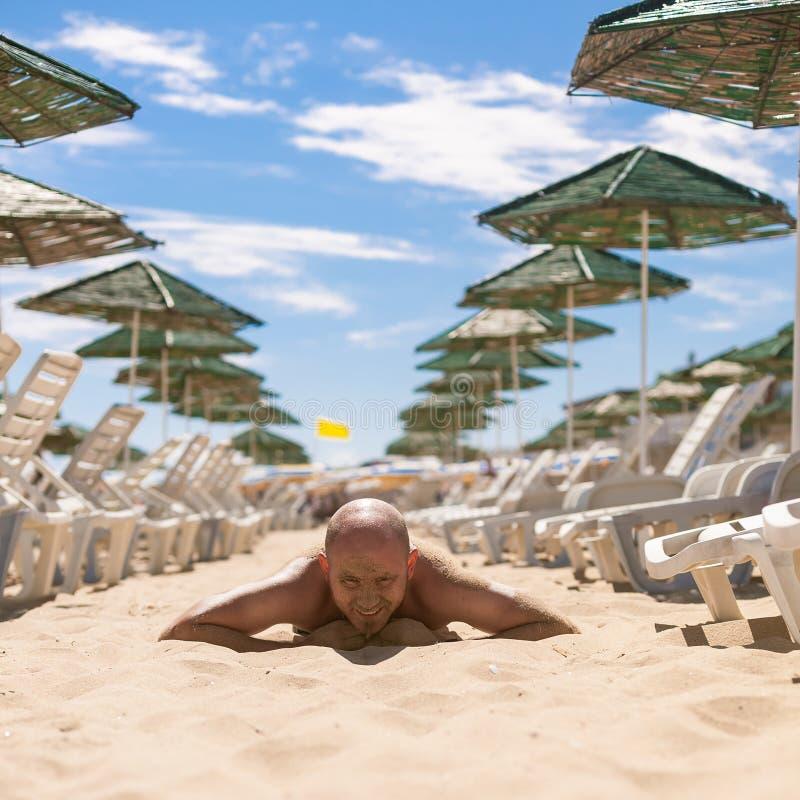 Meia cara de um homem considerável coberto com a areia imagens de stock royalty free