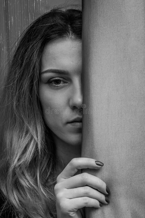 Meia cara de uma menina encantador nova escondida atrás de uma cortina foto de stock royalty free