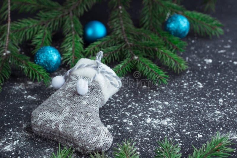 Meia cinzenta do Natal no fundo preto bloqueado pela neve com azul foto de stock royalty free