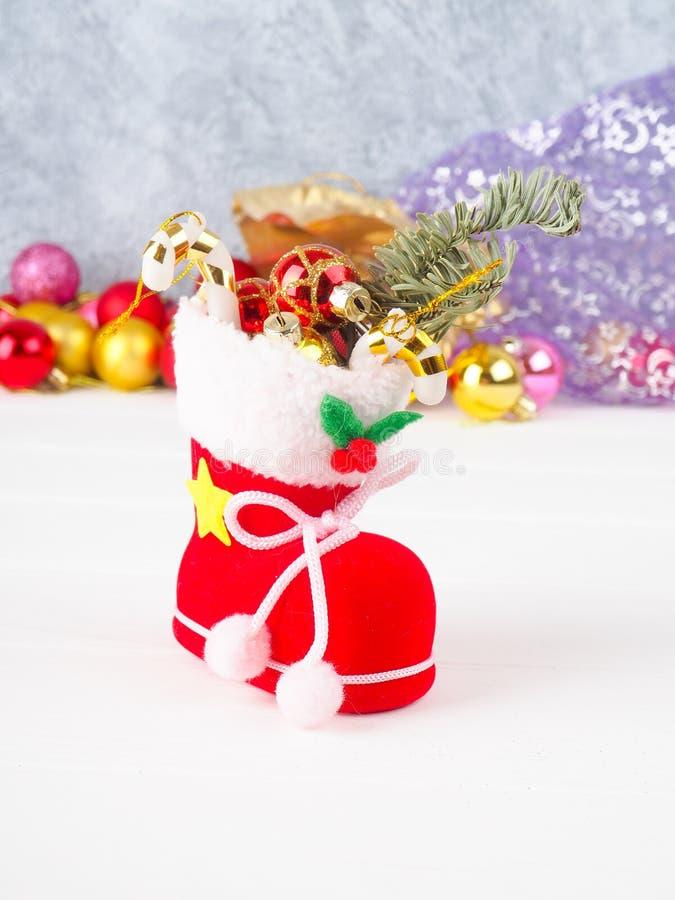 a meia da bota do Natal encheu presentes, azevinho da árvore de Natal do ramo e vara do pirulito imagem de stock