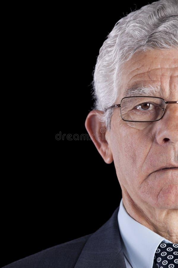 Meia face de um homem de negócios sênior foto de stock royalty free