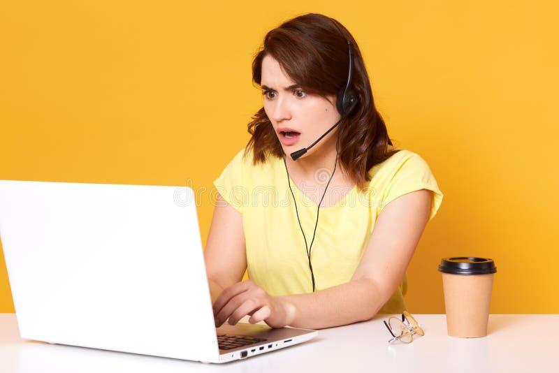 Meia foto do lengh do operador nervoso da jovem mulher que senta-se com boca aberta, olhando a tela do laptopon, sobre amarela foto de stock royalty free