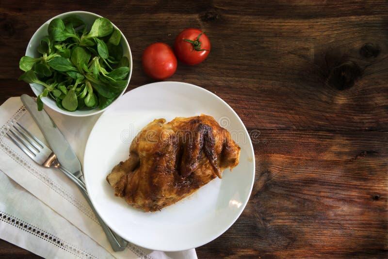 Meia galinha grelhada com cutelaria, salada e tomates em um rusti imagens de stock