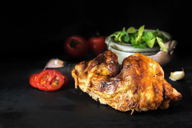 Meia galinha grelhada em uma placa escura da ardósia com salada e tomate imagens de stock royalty free