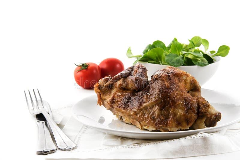 Meia galinha, grelhado friável, com cutelaria, salada e tomates a imagens de stock royalty free