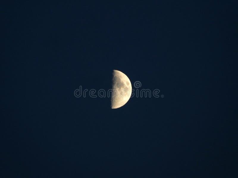 Meia lua amarela de incandescência em uma obscuridade - céu noturno azul imagens de stock royalty free