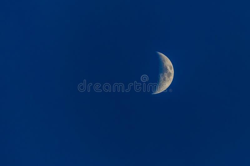 Meia lua branca em escuro - céu azul na noite imagem de stock royalty free