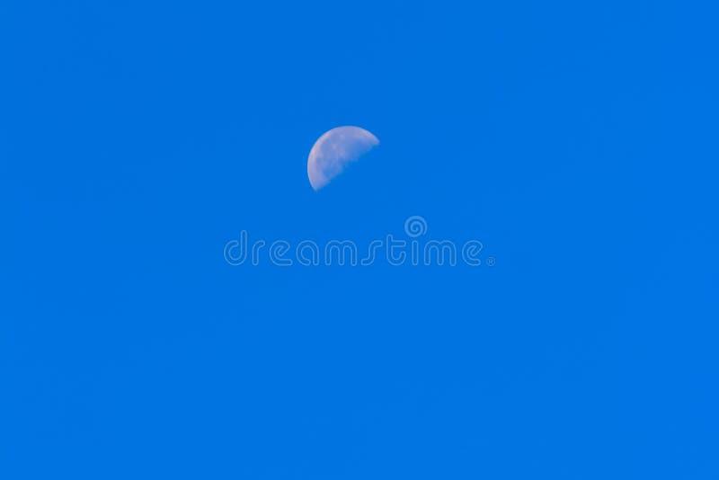 Meia lua durante o dia no céu azul Terra de órbita da lua brilhante dentro fotografia de stock