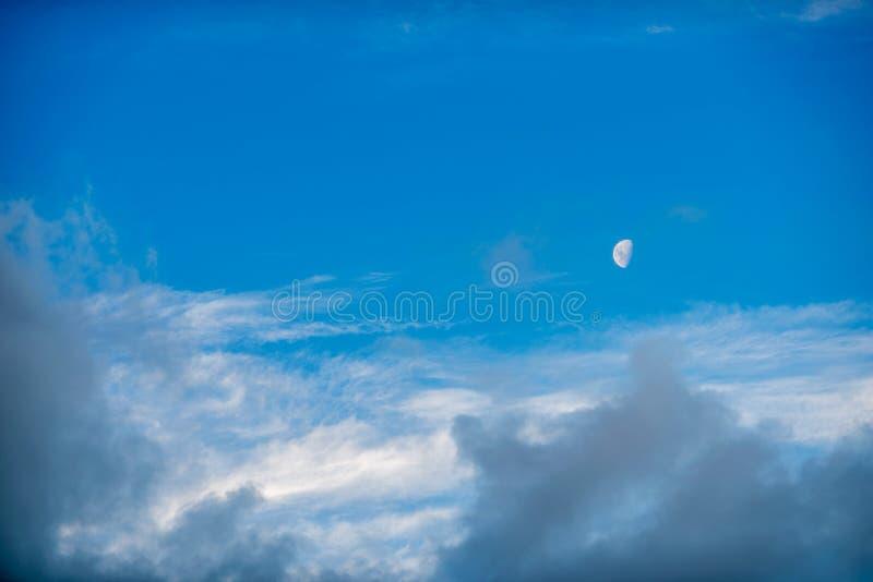 Meia lua que pendura altamente no céu fotografia de stock royalty free
