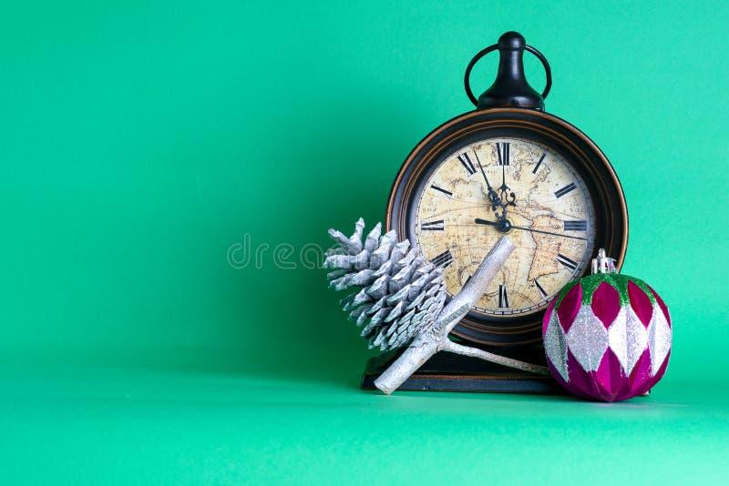 Meia-noite, bauble e cone no galho do pinheiro Contexto verde Cartão de saudação de Natal foto de stock
