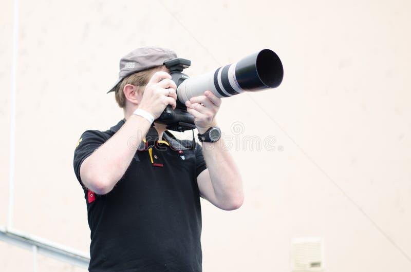 Meia opinião lateral o fotógrafo na camisa preta e no tampão que tomam a foto com câmera do dslr fotografia de stock