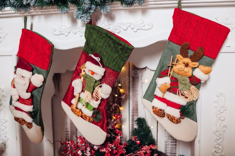 Meias do Natal que penduram sobre a chaminé na meia-noite na Noite de Natal foto de stock