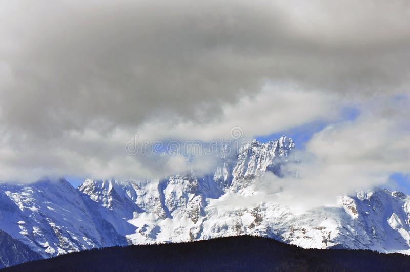 Meili Snow Mountain Mingyong Glaciers. The mountain top under the cloudy sky.Meili Xue Shan or Mainri Snow Mountain is a mountain range in the Chinese province royalty free stock image