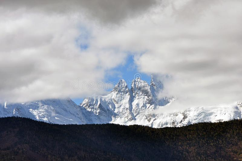 Meili Snow Mountain Mingyong Glaciers. The mountain top under the cloudy sky.Meili Xue Shan or Mainri Snow Mountain is a mountain range in the Chinese province stock photography