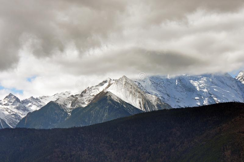 Meili Snow Mountain Mingyong Glaciers. The mountain top under the cloudy sky. Meili Xue Shan or Mainri Snow Mountain is a mountain range in the Chinese province royalty free stock images