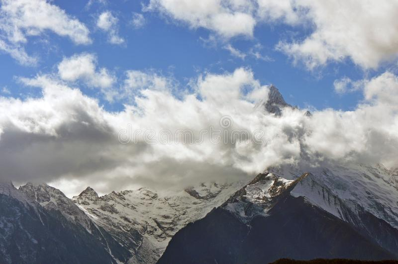 Meili Snow Mountain Mingyong Glaciers. The mountain top under the cloudy sky.Meili Xue Shan or Mainri Snow Mountain is a mountain range in the Chinese province stock images