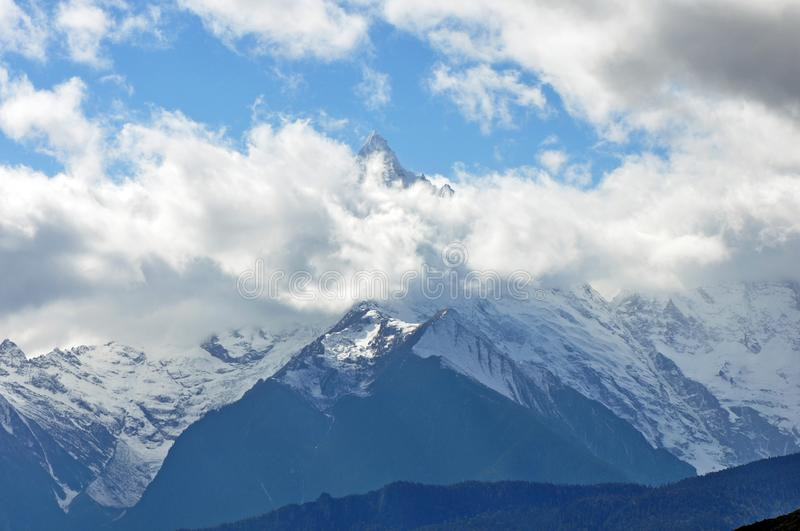 Meili Snow Mountain Mingyong Glaciers. The mountain top under the cloudy sky.Meili Xue Shan or Mainri Snow Mountain is a mountain range in the Chinese province stock photo