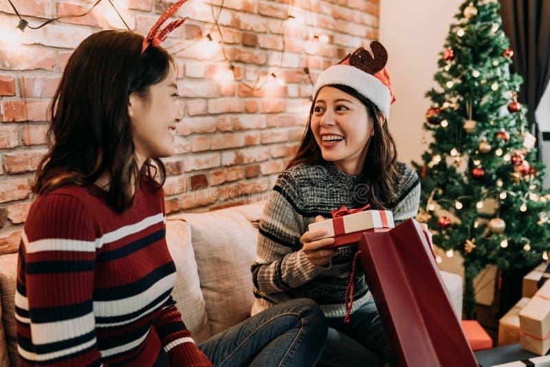 Meilleurs amis échangeant des cadeaux de Noël à la maison images stock