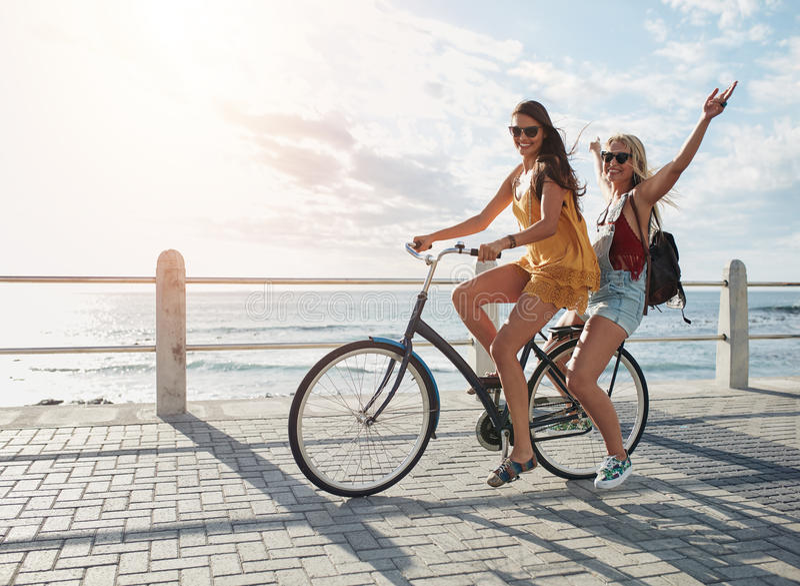 Meilleurs amis ayant l'amusement sur un vélo image libre de droits