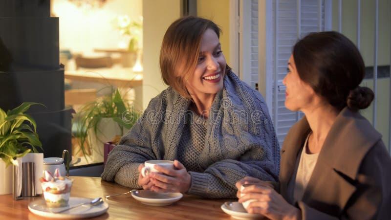 Meilleurs amis partageant des souvenirs d'enfant en café, se regardant, café potable images libres de droits
