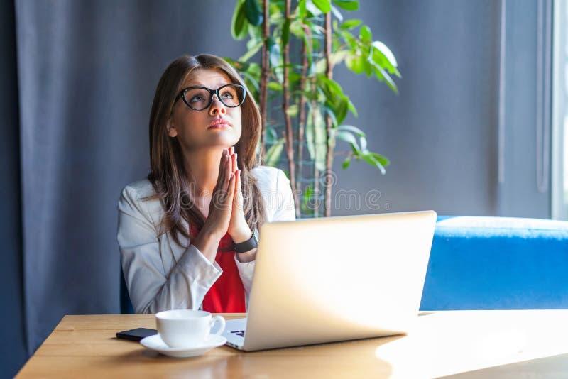 Mein Gott, bitte helfe mir oder vergib mir Portrait der Sorge stilstilvolle Brunette junge Frau in Brille sitzen, aufschauen, Plä lizenzfreie stockfotografie