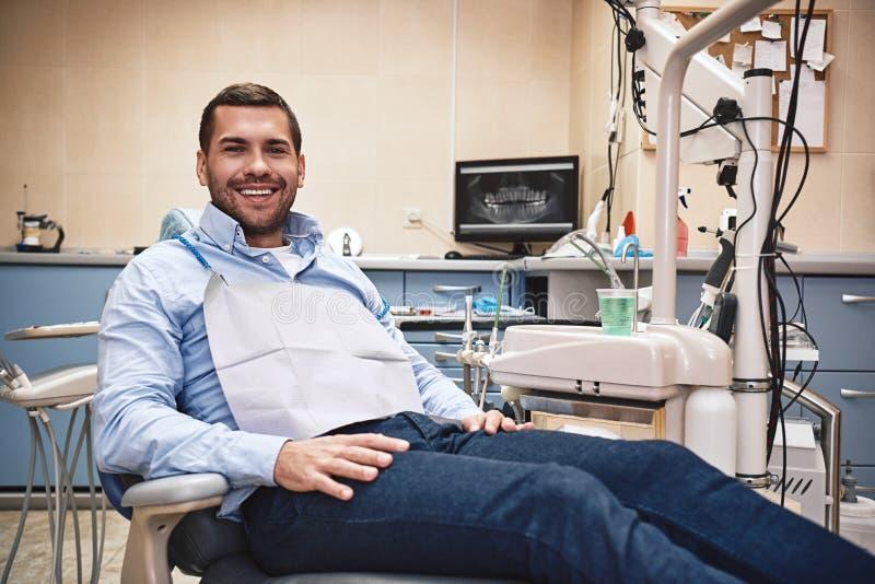 Mein L?cheln ist perfekt! Portr?t des gl?cklichen Patienten im zahnmedizinischen Stuhl lizenzfreies stockfoto
