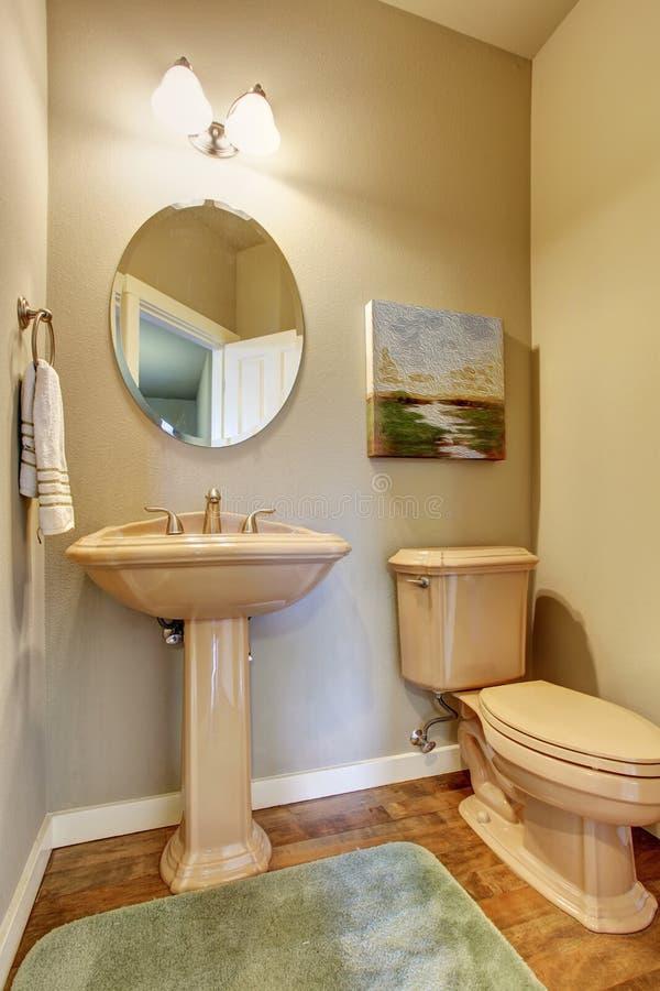 Meio banheiro pequeno com os assoalhos de madeira duros fotografia de stock royalty free