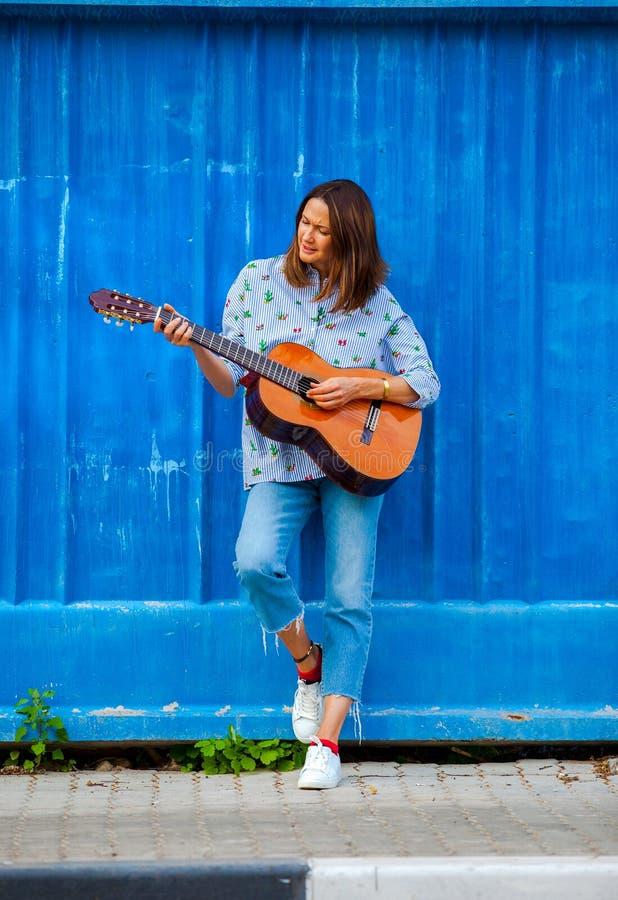 Meio bonito mulher envelhecida com uma guitarra imagens de stock royalty free