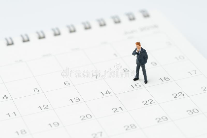 Meio do mês para o homem do salário, conceito do espaço temporal ou da programação, indivíduo diminuto do escritório do homem de  foto de stock royalty free