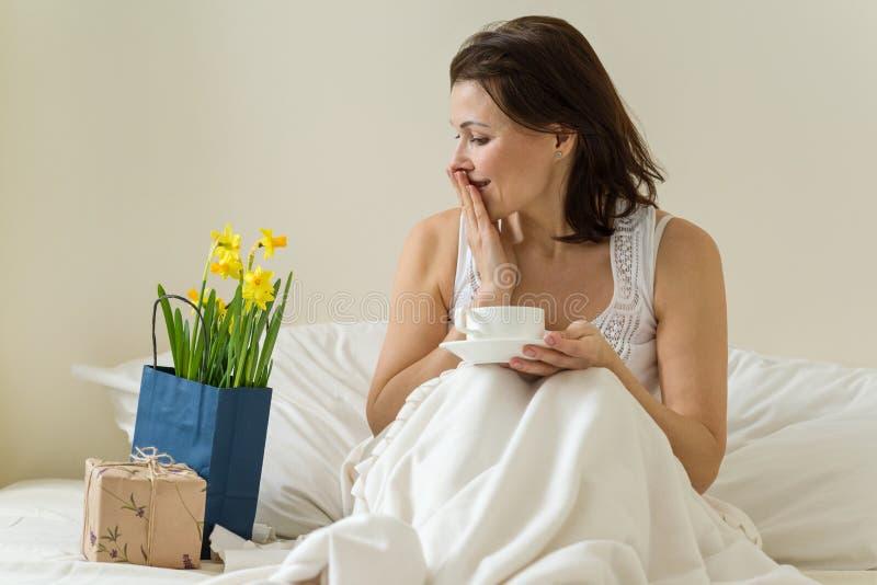 Meio feliz atrativo a fêmea envelhecida da mulher é satisfeito com presente, ramalhete das flores que sentam-se na manhã na cama  fotografia de stock royalty free