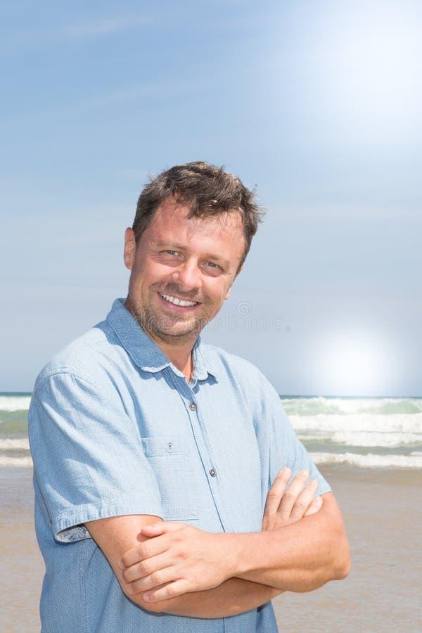 meio feliz os braços envelhecidos do homem cruzaram-se na praia imagem de stock royalty free