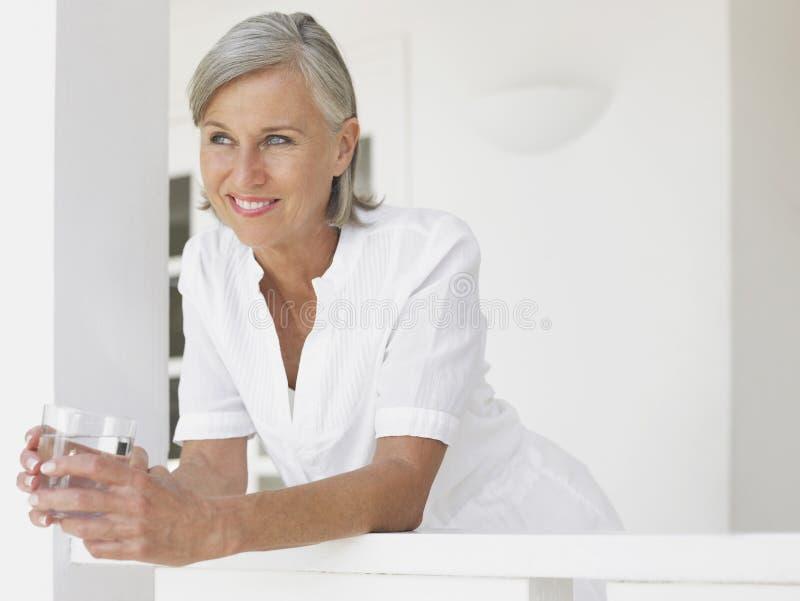 Meio feliz pensativo mulher envelhecida que olha afastado imagem de stock
