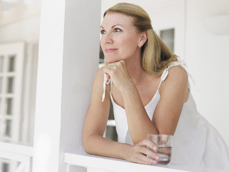 Meio feliz pensativo mulher envelhecida que olha afastado imagem de stock royalty free