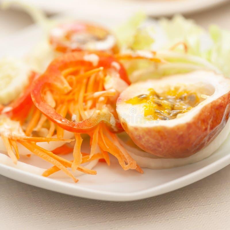 Meio fruto de paixão com salada fresca na placa branca na tabela branca foto de stock royalty free