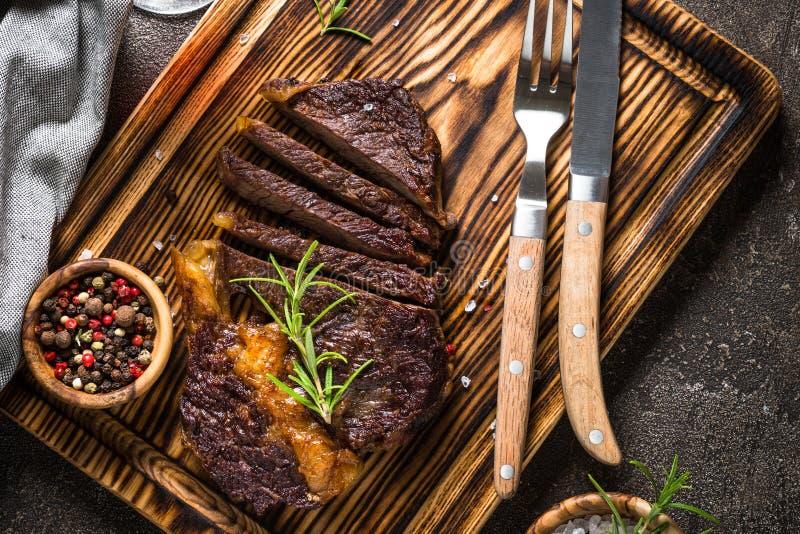 Meio grelhado do bife bem na placa de corte de madeira fotos de stock royalty free