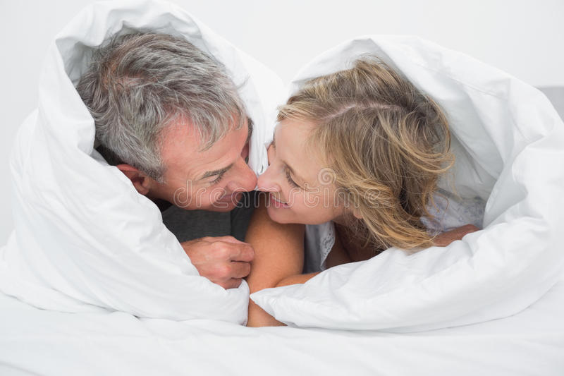 Meio loving pares envelhecidos sob a edredão imagem de stock