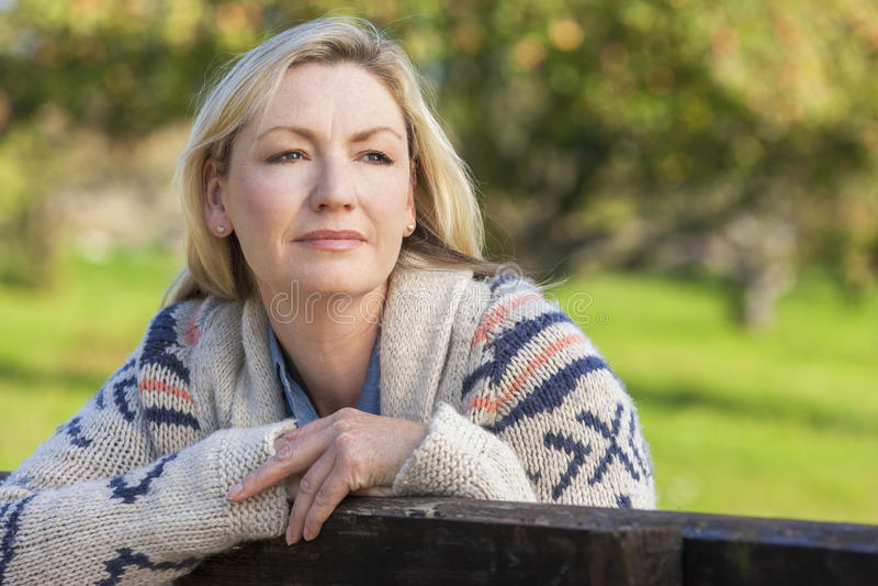 Meio pensativo atrativo mulher envelhecida que descansa na cerca imagem de stock royalty free