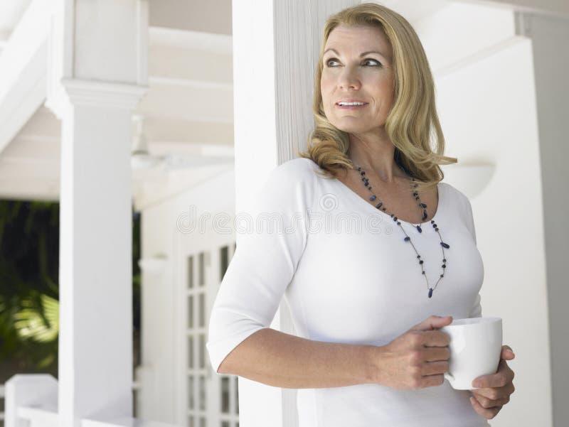 Meio pensativo mulher envelhecida com o copo que olha afastado fotografia de stock