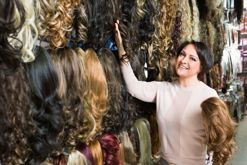 Meio positivo mulher envelhecida que compra a extensão do cabelo fotografia de stock