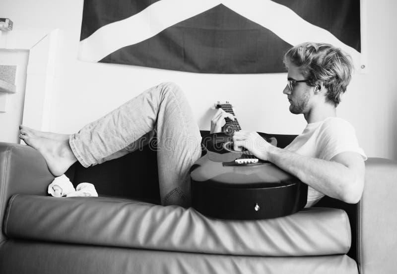 Meio preto e branco do estilo da imagem do vintage disparado do homem novo que encontra-se no sofá e que joga na guitarra na sala imagens de stock royalty free