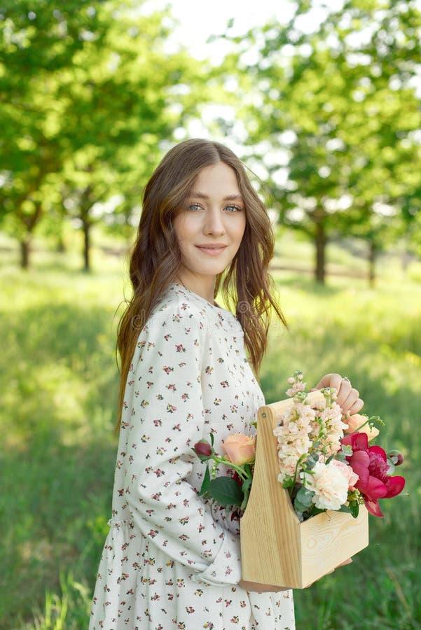Meio retrato de uma mulher positiva encantador vestida em vestidos brancos longos do verão com um sorriso feliz no fundo de um ve foto de stock