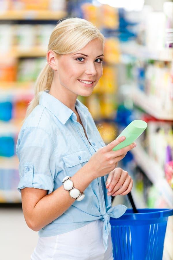 Meio retrato do comprimento da menina na loja que escolhe cosméticos foto de stock