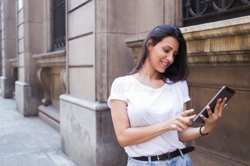 Meio retrato do comprimento de uma mulher latin de sorriso que olha a foto em seu tablet pc digital ao andar na rua fotografia de stock royalty free
