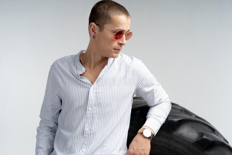 Meio retrato do comprimento do homem novo bonito em ?culos de sol vermelhos, camisa branca vestindo, inclinada no pneu grande, is fotos de stock