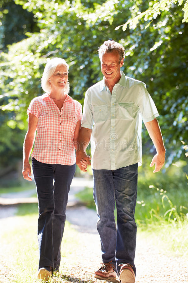 Meio romântico pares envelhecidos que andam ao longo do trajeto do campo fotografia de stock royalty free