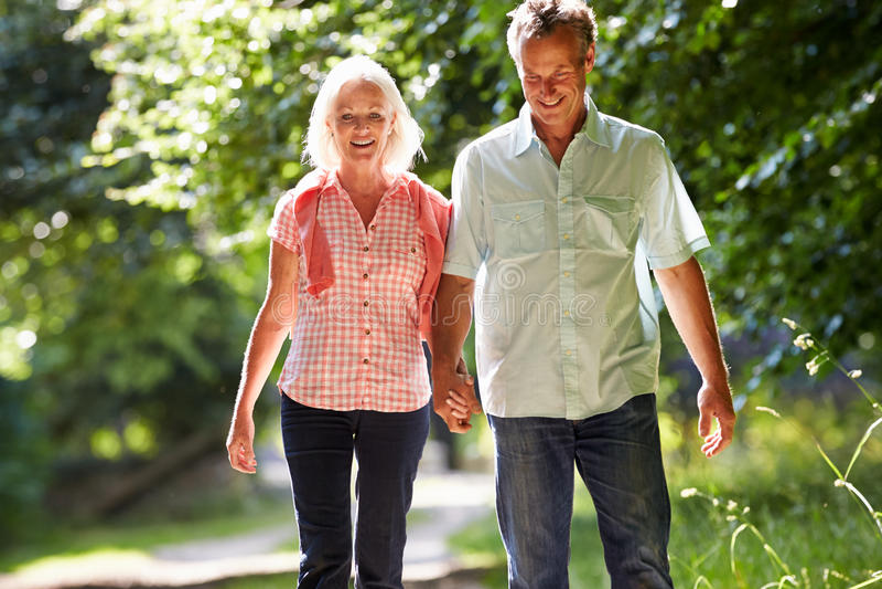Meio romântico pares envelhecidos que andam ao longo do trajeto do campo imagem de stock