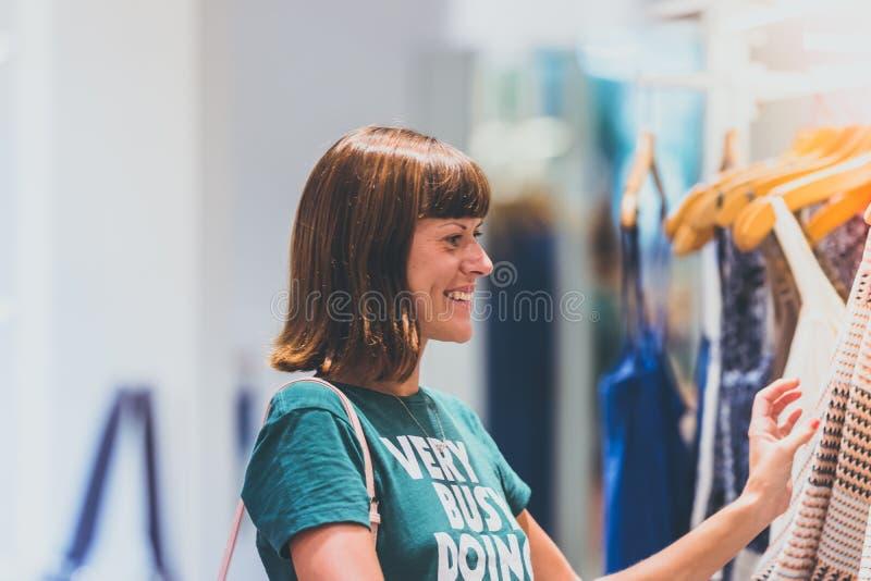 Meio tiro do corpo de uma jovem mulher feliz que olha a roupa que pendura no trilho dentro da loja da roupa na ilha de Bali fotos de stock